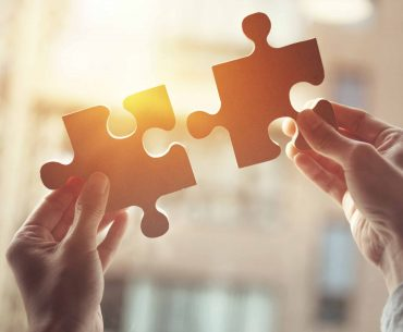 man putting puzzle pieces together to resemble the importance of marketing strategy